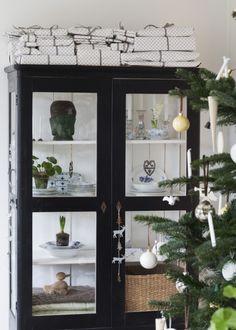 ET MAGISK JULEHJEM MED HJEMMELAVET PYNT: På toppen af det gamle vitrineskab står julens mange pakker. De er pakket smukt og kreativt ind, og familien har hygget sig med den flotte indpakning. [...] De tre meter til loftet i familiens hjem ved København giver rigeligt med plads til julerier og hygge, når hele familien bliver samlet til advent med gløgg og æbleskiver – og en kælketur, hvis der er sne | Mad & Bolig