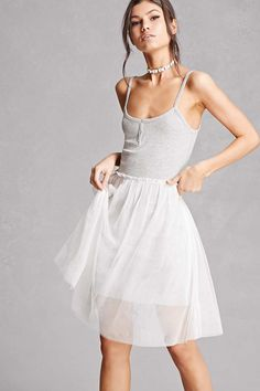 A combo dress by English Factory™ featuring a ribbed knit bodice, Henley placket, cami straps, scoop neckline, a tulle skirt, and a ribbed knit underlay.