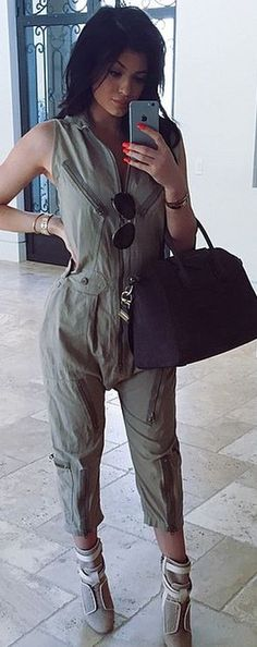 Who made   Kylie Jenner's green jumpsuit, gray handbag, boots, and gold jewelry?