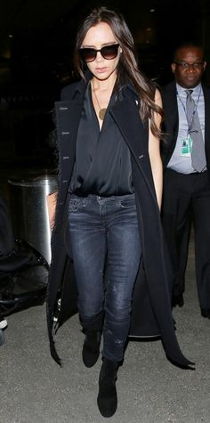 Victoria Beckham landed in LAX in the chicest travel ensemble—she layered a black sleeveless coat over a draped black top and dark rinse skinnies, and styled the combo with a statement gold pendant, a nude clutch, and black boots.