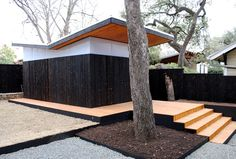 This former backyard shed, now an office, designed by THOUGHTBARN, effectively plays with materials and form, rooting the compact structure with charred siding. The dark siding is topped with light-diffusing polycarbonate sheets and a butterfly roof. Western red cedar was carbonized for both the building and the fence.