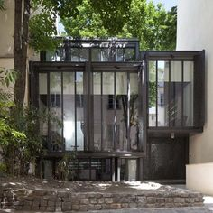 Steps connecting the gradually rising floors of this Paris house can be glimpsed through the cut-out shutters on its glazed facade.