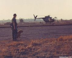 A dog handler with a combat tracker team from the 4th Inf. Det. (War Dog Provisional), waits at the helipad for a flight to a combat area. February 1969 - The National Archives / SP5 Bryan K. Grigsby