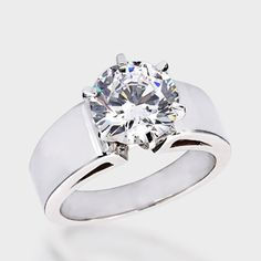 This high quality cubic zirconia ring features a 3.0 carat brilliant round stone set in a raised six-prong wide band. This ring is available in solid 14K white gold or 14K yellow gold. Cubic zirconia weights refer to equivalent diamond carat size.