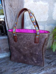 Tough leather bag with hot pink leather interior and fab Aztec stitched handle... This and more from Consuela are available at our Boerne, Texas boutique Daisy Pearl!  www.facebook.com/daisypearlboutiqueboerne