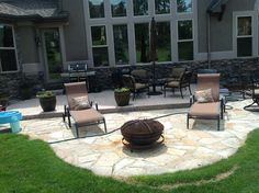 "Front view patio with uneven flaking flagstone and rusted ""fire pit""."