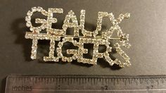 """Cheer on the LSU Tigers wearing one of these Geaux Tigers Rhinestone Pins. Rhinestones are clear in a silver tone setting. Pins are 3"""" wide x 2 """" tall and have a pin back. Perfect for fundraising, for Sorority Sisters, for Loyal Fans. Pins are new in cellophane. Ships from Illinois. 9 pins are available. Email tammy@blessingsandbling.com for purchase info."""