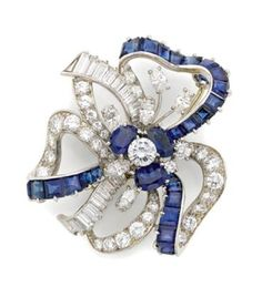 Sapphire and Diamond Bow Brooch, Oscar Heyman Bros.   Platinum, the looped ribbons centering one round diamond approximately .50 ct., encircled by 3 oval sapphires, accented by 6 marquise-shaped diamonds, the ribbons set with 19 baguette and 36 round diamonds, altogether approximately 5.70 cts., embellished by 25 square-cut sapphires, with maker's mark for Oscar Heyman Bros., approximately 13.2 dwt.