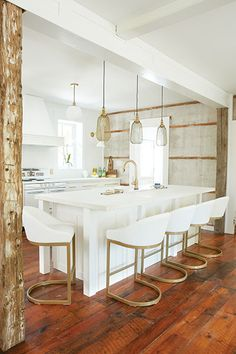 All-white elegance  The orginial concrete walls of this kitchen were left exposed, creating an interesting contrast between chic and rustic.