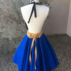 This is an adult size Anna costume apron. Made of cotton. Top is handrawn appliqué that is embroidered in place. The skirt is a wrap style that provides full coverage in back yet is adjustable to fit many sizes. Designed to overlap in back with ties that go through buttonholes on the waist
