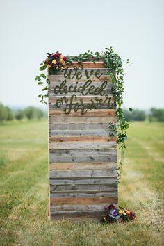 "Summer Harvest wedding inspiration wood palette ceremony backdrop with moss lettering ""we've decided on forever"""