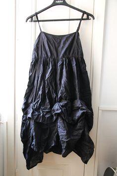 Musta Kappahlin mekko, jonka helma on jännästi rypytetty ja kellomainen.