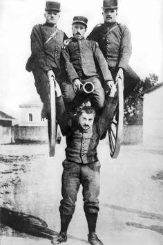 A strongman in the French army lifting a cannon overhead along with three of his comrades astride it, 1917.