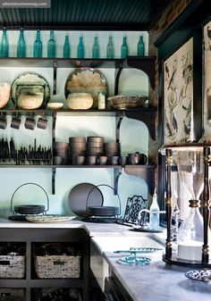 kitchen with marble counter, open shelves, bottle collection, huge hour class on counter, beautiful  focus-damnit: (via House of Turquoise)