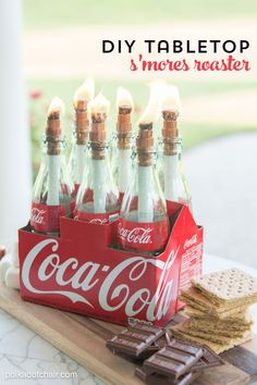 DIY tabletop s'mores maker made from upcycled Coca-Cola bottles.Cute idea for a backyard party.