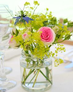 Simple glass vessels housed organic flower arrangements for a destination wedding on the English countryside.