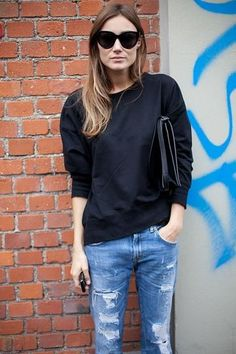 casual street style - a leather clutch and cool shades elevate this relatively ordinary outfit of a plain black sweatshirt + super-distressed jeans.