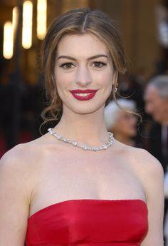 Anne Hathaway vestido rojo labios rojos collar de diamantes pendientes rizos castaños Oscar