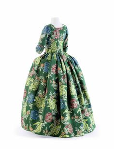 1730-1740, England - Gown in dark-green Gros de Tour brocade.This gown with adjusted back is typical of English ladies' fashion during the 18th century and is outstanding in the quality of its stiff, beautifully brocaded silk, with its pattern of tulips and chrysanthemum flowers.
