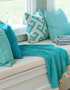 Sunbrella pillows and throw brighten a window seat.
