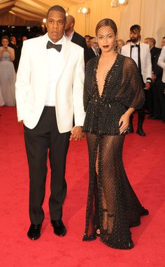 While Jay Z lightened up in a white jacket, Beyoncé went to the dark side in her Givenchy Haute Couture crystal-embroidered, studded gown that she teamed with embroidered fishnet tights. #MetGala