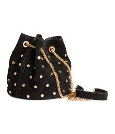 PREMIUM QUALITY. En liten bucketväska i mocka med runda nitar. Väskan har axelrem av metallkedja och knäppning med tryckknapp. Textilfodrad. Diameter 14 cm, höjd 16 cm.