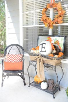 Throw pillows on swing & chairs, pumpkin on spider planter, assorted mini orange & white pumpkins on/ around table