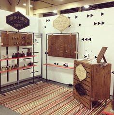 Son of Sailor Booth Display. Love the leather holding the boards to dark pipes and the neon edge of the wooden shelves