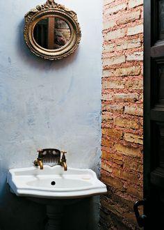 Ladrillo de tejar y lavabo de pedestal y grifería retro. En la pared un espejo antiguo. No hace falta más, un estupendo resultado para un baño de servicio.