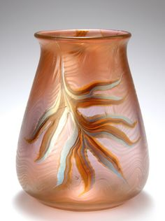 Loetz vase, c. 1900, Phaenomen Gre 692. Glass in peach-color shades. Surface with irregular translucent melted threading. Two leaf motives in silver-yellow and honey-brown with brown veins, matt iridescent. Marked. H. 17.5 cm.