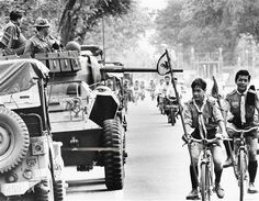Rebel troops with guns move in armored vehicles in Saigon on Sept. 13, 1964 during coup against Vietnamese Premier Nguyen Khanh. At right are boy scouts on bicycles. (AP Photo)    Use Information This content is intended for editorial use only.  For other uses, additional clearances may be required.  ID: 6409130363