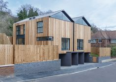 Twin wooden houses by Adam Knibb Architects are raised up above street level.