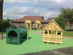 Playground equipment above a green wet pour safety surface