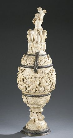"""A German, 19th century silver and carved ivory ewer. Carved ivory in high relief(possibly Mastodon) having figural adornment of a bacchanal scene. With silver and silver gilt bands, base, and handle. Marked on bottom with K, crescent and crown, and 925. 20 1/2"""" h to top of handle. 16 1/2"""" to top of lip."""