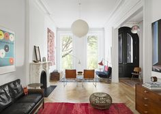 The living room in Brent Allen Buck's finished Brooklyn Brownstone. The red rug and globe pendant light really stand out in the airy space.