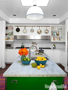 Over a custom hood in the gleaming white kitchen, the designers hung pots and pans from a meat hook found at a flea market. Design: Nickey Kehoe.