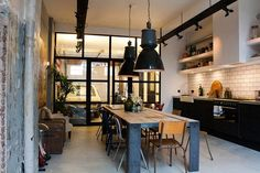 cuisine et salle à manger 2 en 1, aménagées avec des meubles en noir, blanc et bois et deux suspensions industrielles noires
