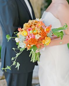For this desert wedding, the bride carried a bright bouquet made of peonies, ranunculus, poppies, Mokara orchids, Cymbidium orchids, coxcomb, protea, and succulents.