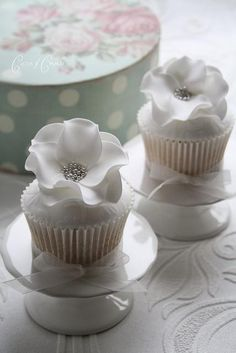 The perfect wedding cupcakes! This confectionery creation is simple and elegant with the right amount of sparkle. Small pedestals set the stage for this cupcake wrapped in a simple white cupcake wrapper, iced with white icing and topped off with a large white flower made of sugar; let us not forget the silver bead sprinkles that gather in the middle to top off this unique treat. Ask your bakery or cake-maker if they could replicate this work of art for your special day!