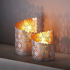 """Let the warm glow of candlelight shine through the traditional Jali pattern cut into the sides of this spiraled metal candleholder from Tara Projects in India. Tara works to change the lives of India's """"untouchables"""" by eliminating unfair trade practices and child labour. Group with larger size (6827637)."""