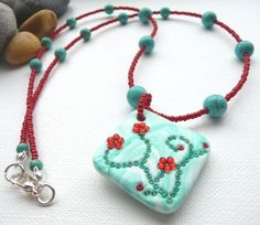 My Handmade Polymer Clay Flower Pendant, in a turquoise/green colour with deep red seed beads and turquoise semi precious gemstones.  Lovely for Spring/Summer.
