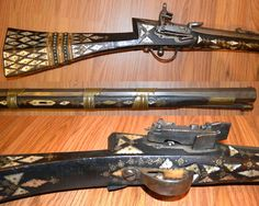 Ottoman miquelet rifle, 18th century, 28 1/2 inch .50 cal barrel, with swamped muzzle, mounted with a copper sight and deeply rifled. The open rear sight has a hinged graduated peep sight. The miquelet lock is of fine quality. The wood stock is profusely inlaid with scalloped edge mother of pearl diamonds and triangles and the field with brass piques and wheel shaped inlays. The butt with alternate bands of brass inlaid ivory and brass tacks.