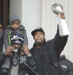 Ravens player Terrell Suggs lifts the Lombardi Trophy outside City Hall. Ravens Players, Football Players, Terrell Suggs, Lombardi Trophy, Parade Route, Victory Parade, Baltimore Ravens, Victorious