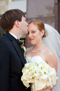 bride in veil and pearl necklace smiles at camera @myweddingdotcom
