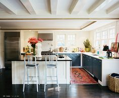 I <3 everything about this kitchen. Love that they didn't paint the rest of the cabinet, it seems to frame the blue and gives it more of a punch. Plus, I love the rug, the pattern hides stains and it looks sooo much better than regular mats.