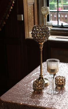 the richness of a room with gold tealight holders on a rose gold sequinned cloth and dark oak panelling