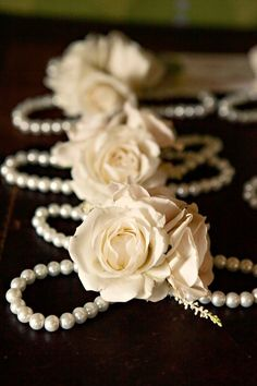 The mothers and house party will wear ivory spray roses and gray dusty miller on pearl bracelets.