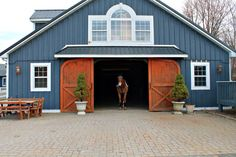Pretty blue barn with contrasting brown doors. Beautiful barn idea for equestrians!