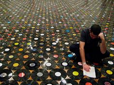 Floor tiled completely in vinyl albums!  I could have a great afternoon just reading the floor!