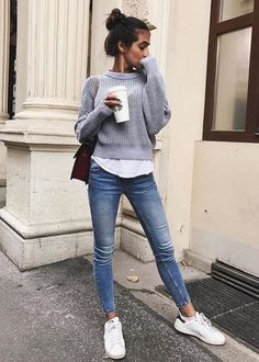 Gray sweater over white tee with blue jeans.